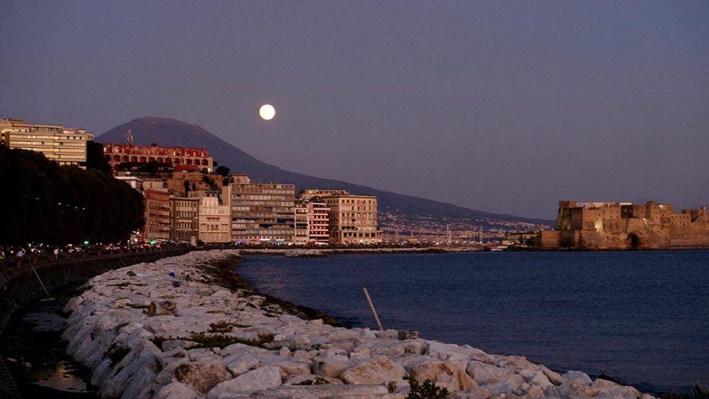 Strandpromenaden med fullmånen som titter fram bak Vesuv.